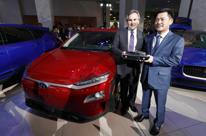 Brian Smith, left, Chief Operating Officer, Hyundai Motor America and Yong-woo William Lee, President and CEO of Hyundai Motor North America hold the North American SUV of the Year trophy next to the Hyundai Kona award during media previews for the North American International Auto Show in Detroit, Monday, Jan. 14, 2019. (AP Photo/Paul Sancya)