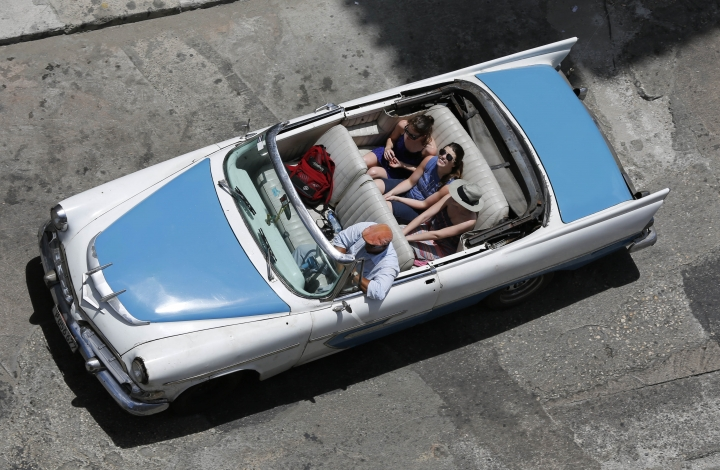 FILE - In this May 13, 2015, file photo, tourists ride a classic American convertible in Havana, Cuba. President Donald Trump's Cuba policy is driving hundreds of millions of dollars from the island's private entrepreneurs to its military-controlled tourism sector, the opposite of its supposed goal, new statistics say. (AP Photo/Desmond Boylan, File)