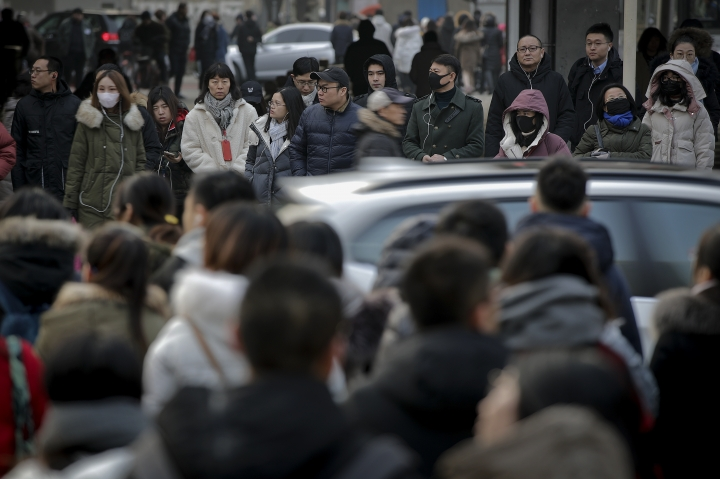 Pedestrians wait to cross a traffic intersection at the Central Business District in Beijing, Monday, Jan. 14, 2019. China's 2018 trade surplus with the United States surged to a record $323.3 billion but exports contracted in December as the delayed impact of President Donald Trump's tariff hikes started to depress demand. Global exports shrank 4.5 percent in December, reflecting weak consumer demand. (AP Photo/Andy Wong)