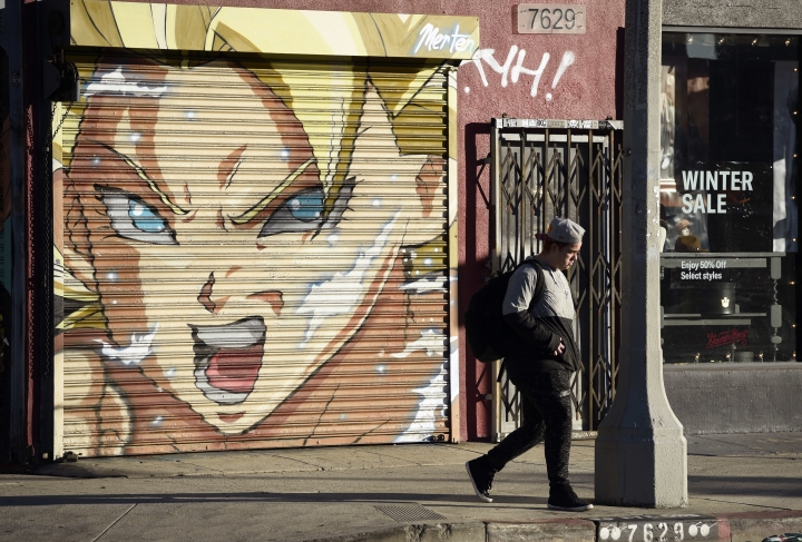 "This Jan. 9, 2019 photo shows a pedestrian walking past a mural depicting ""Caulifla"" by artist Jake Merten inspired by the ""Dragon Ball"" anime series in Los Angeles. ""Dragon Ball"" is a revered anime that has influenced pop culture for years, earning praise from the likes of Michael B. Jordan, Ronda Rousey and Chris Brown, showing up in end zone celebrations and even at the Macy's Thanksgiving Day Parade. With the new film ""Dragon Ball Super: Broly"" releasing this week in the U.S., the franchise's popularity with its famous and non-famous fans is likely to grow. (AP Photo/Chris Pizzello)"