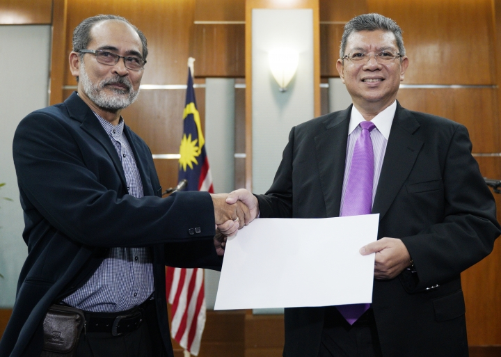 Malaysia Foreign Minister Saifuddin Abdullah, right, receive a memorandum from Mohd Mazarin Bin Ismail, chairman of Boycott, Divestment and Sanctions (BDS) Malaysia, before a press conference in Putrajaya, Malaysia, Wednesday, Jan. 16, 2019. Malaysia's foreign minister says the government will not budge over a ban on Israeli athletes in para swimming competition and decided that the country will not host any events in future involving Israel. (AP Photo/Yam G-Jun)