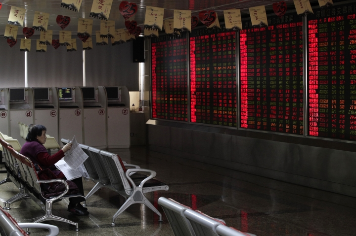 A woman reads a newspaper at a brokerage house in Beijing, Friday, Jan. 18, 2019. Chinese stocks rose Friday on signs of possible progress in negotiations over Beijing's tariff war with Washington. (AP Photo/Andy Wong)