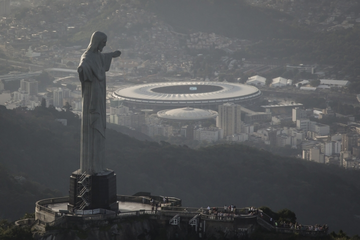 "FILE - This May 13, 2014, file photo, shows an aerial view of Maracana stadium behind the Christ the Redeemer statue, in Rio de Janeiro, Brazil. The U.N. culture and education agency has recognized Rio de Janeiro, on Friday, Jan. 18,2 019, as the ""World Capital of Architecture"" for 2020. (AP Photo/Felipe Dana, File)"