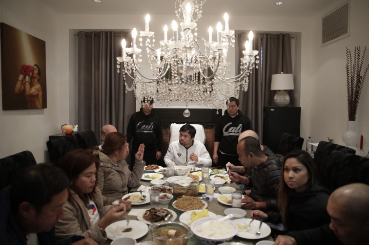 Boxer Manny Pacquiao, center, eats his breakfast with friends and relatives following his morning run Monday, Jan. 14, 2019, in Los Angeles. Breakfast at Manny Pacquiao's house began with a silent prayer, followed by more silence around the big dining room table as his entourage waited for the fighter to take the first bite. (AP Photo/Jae C. Hong)