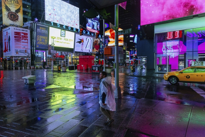 A man wearing a plastic poncho walks through Times Square in the early morning Sunday, Jan. 20, 2019, in New York. The National Weather Service said on Saturday that a dramatic drop in temperatures could turn the weekend's rainfall into ice before Monday. (AP Photo/Kevin Hagen)