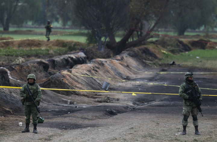 Soldiers guard the site where a gas pipeline exploded two days prior, in the village of Tlahuelilpan, Mexico, Sunday Jan. 20, 2019. A massive fireball that engulfed locals scooping up fuel spilling from a pipeline ruptured by thieves in central Mexico killed dozens of people and badly burned dozens more on Jan. 18. (AP Photo/Claudio Cruz)