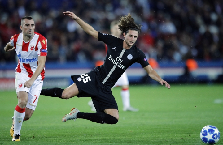 FILE - In this Oct. 3, 2018, file photo, PSG midfielder Adrien Rabiot is challenged by Red Star's Nenad Krstici, left, during a group C Champions League soccer match between Paris Saint Germain and Red Star Belgrade at the Parc des Princes stadium in Paris. Coach Thomas Tuchel needs Rabiot back in the side because an injury to Marco Verratti left Paris Saint-Germain seriously short of options in midfield. (AP Photo/Francois Mori, File)
