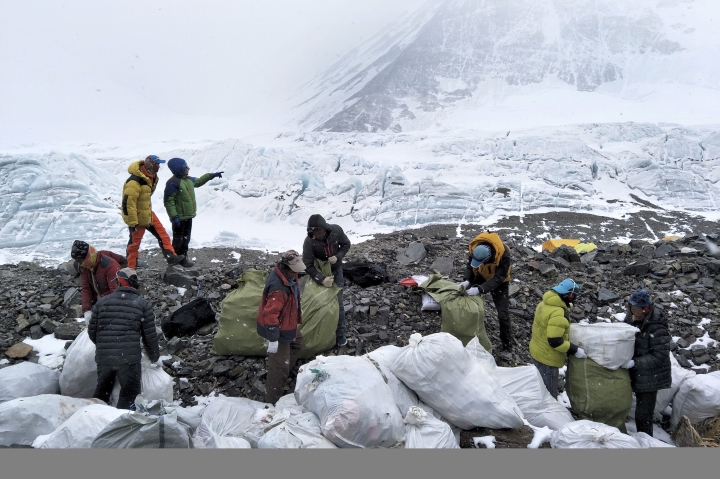 FILE - In this May 8, 2017, file photo released by Xinhua News Agency, people collect garbage at the north slope of the Mount Qomolangma in southwest China's Tibet Autonomous Region. China announced Monday, Jan. 21, 2019 that it plans to cut the number of climbers attempting to scale Mount Everest from the north by 1/3 this year as part of plans for a major cleanup on the world's highest peak. (Awang Zhaxi/Xinhua via AP)