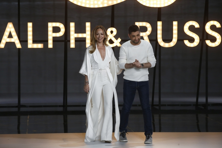Designers Tamara Ralph, left, and Michael Russo accept applause at the end of the Ralph & Russo Spring/Summer 2019 Haute Couture fashion collection presented in Paris, Monday Jan. 21, 2019. (AP Photo/Michel Euler)