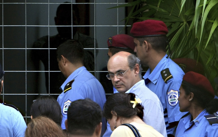 """FILE - In this Oct. 11, 2008 file photo, journalist Carlos Fernando Chamorro, who runs the Communication Research Center, Cinco, is surrounded by the police as a search warrant is carried out at Cinco's facilities in Managua, Nicaragua. The prominent Nicaraguan journalist announced in a video posted Monday, Jan. 21, 2019 to his Confidencial Facebook page that he had taken """"the painful decision to go into exile to ensure my freedom and physical safety, and above all to carry on independent journalism from Costa Rica."""" (AP Photo/Esteban Felix, File)"""