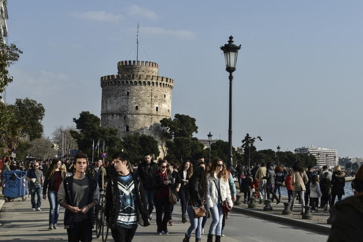 FILE - In this Sunday, March 15, 2015 file photo, people walk on the main seaside avenue, as the White Tower is seen at the background, in the Greek northern town of Thessaloniki. Greece's government says it has removed hundreds of archaeological museums, ancient sites and castles inadvertently put on a provisional list of properties up for private development under the country's bailout terms. (AP Photo/Giannis Papanikos, File)
