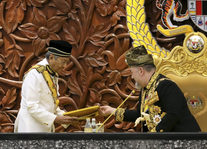 FILE - In this July 17, 2018, file photo, Malaysian Prime Minister Mahatir Mohamad, left, passes the opening speech to King Sultan Muhammad V during the opening of the 14th parliament session at the Parliament House in Kuala Lumpur, Malaysia. Sultan Muhammad V shocked the nation by announcing his abdication in January 2019, days after returning from two months of medical leave. The 49-year-old sultan from eastern Kelantan state only reigned for two years as Malaysia's 15th king and didn't give any reason for quitting. (AP Photo/Yam G-Jun, File)