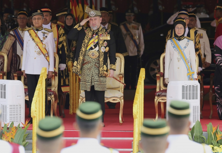 FILE - In this July 17, 2018, file photo, Malaysian King Sultan Muhammad V, center, salutes during the national anthem with Prime Minister Mahatir Mohamad, left, and Deputy Prime Minister Wan Azizah Wan Ismail, right, at the opening of the 14th parliament session at the Parliament House in Kuala Lumpur, Malaysia. Sultan Muhammad V shocked the nation by announcing his abdication in January 2019, days after returning from two months of medical leave. The 49-year-old sultan from eastern Kelantan state only reigned for two years as Malaysia's 15th king and didn't give any reason for quitting. (AP Photo/Yam G-Jun, File)