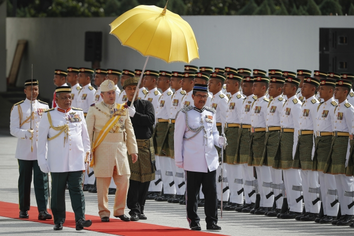 FILE - In this Dec. 13, 2016, file photo, Malaysian King Sultan Muhammad V, third from left, inspects a ceremonial guard of honor during his welcome ceremony in Kuala Lumpur, Malaysia. Sultan Muhammad V shocked the nation by announcing his abdication in January 2019, days after returning from two months of medical leave. The 49-year-old sultan from eastern Kelantan state only reigned for two years as Malaysia's 15th king and didn't give any reason for quitting.AP Photo/Vincent Thian, File)