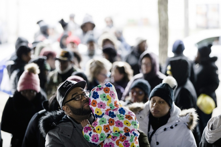 Anthony Spencer, whose wife, Chastity, right, is a furloughed federal worker, holds his daughter, Sydney, as they wait in line with others who are affected by the partial government shutdown for Philabundance volunteers to distribute food under Interstate 95 in Philadelphia, Wednesday, Jan. 23, 2019. (AP Photo/Matt Rourke)