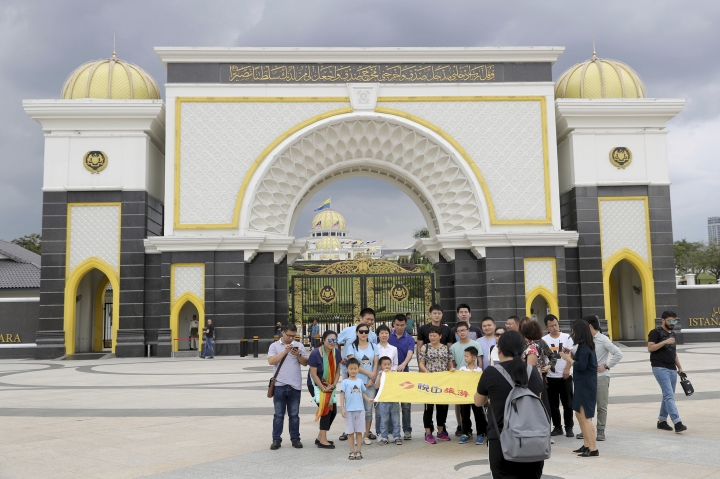Tourists take photos in front of Malaysia National Palace in Kuala Lumpur, Malaysia, Thursday, Jan. 24, 2019. King Sultan Muhammad V shocked the nation by announcing his abdication in January 2019, days after returning from two months of medical leave. The 49-year-old sultan from eastern Kelantan state only reigned for two years as Malaysia's 15th king and didn't give any reason for quitting. Sultan Abdullah Azlan Shah succeeded his ailing 88-year-old father on Jan. 15, in a move seen as paving the way for him to become the next king. (AP Photo/Vincent Thian)