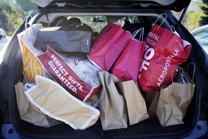 FILE- In this Nov. 23, 2018, file photo shopping bags are stuffed into a car at Prime outlets on Black Friday in Lee, Mass. The holiday season was a brutal one for U.S. retailers, especially department stores and companies that sell luxury products. (Ben Garver/The Berkshire Eagle via AP, File)