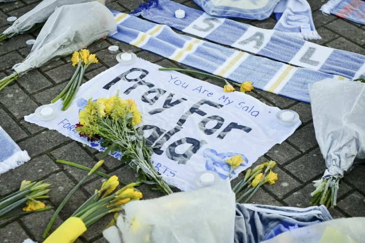 Flowers and tributes are placed outside Cardiff City Football Club, Wales, Wednesday Jan. 23, 2019, after a plane with new signing Emiliano Sala on board went missing over the English Channel on Monday night. The search resumed Wednesday to find missing Emiliano Sala and his pilot with authorities in the Channel Islands prioritizing whether they have been unable to make contact after more than 36 hours having managed to land, been picked up by a ship or are still on a lifeboat. (Ben Birchall/PA via AP)