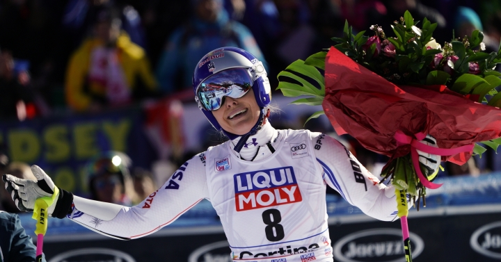 """FILE - In this Sunday, Jan. 20, 2019 filer, United States' Lindsey Vonn holds a bunch of flowers after completing an alpine ski, women's World Cup super-G in Cortina D'Ampezzo, Italy. It seemed like destiny played a role on Sunday when Mikaela Shiffrin won what could very well turn out to be Lindsey Vonn's last race. Vonn broke down emotionally after she failed to finish a World Cup super-G on knees so worn down that she describes them as """"bone on bone."""" Shiffrin then came down nine racers later and won her first speed race at the premier stop on the women's circuit. (AP Photo/Giovanni Auletta, File )"""