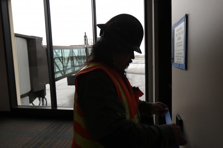 FILE- In this Jan. 23, 2019, file photo Dave McLeod tapes off trim as he prepares to paint a wall near a gate in the new passenger terminal at Paine Field in Everett, Wash. Alaska Airlines says it will delay the start of commercial passenger service at the new terminal by at least three weeks due to the ongoing partial shutdown of the federal government, as the officials who must sign off on a final environmental assessment are on furlough. (AP Photo/Ted S. Warren, File)