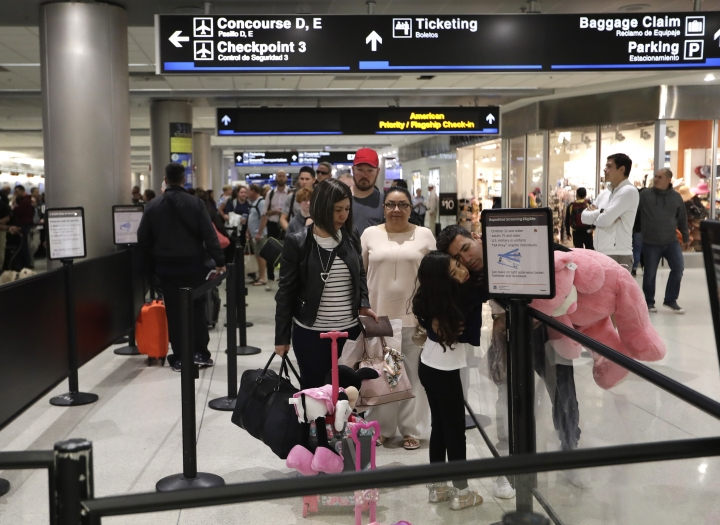 FILE- In this Jan. 18, 2019, file photo Carlos Gonzalez, right, hugs his daughter as she waits in line at a security checkpoint at Miami International Airport in Miami. The strain of a 34-day partial government shutdown is weighing on the nation's air-travel system, both the federal workers who make it go and the airlines that depend on them. Unions that represent air traffic controllers, flight attendants and pilots are growing concerned about safety with the shutdown well into its fifth week. (AP Photo/Lynne Sladky, File)