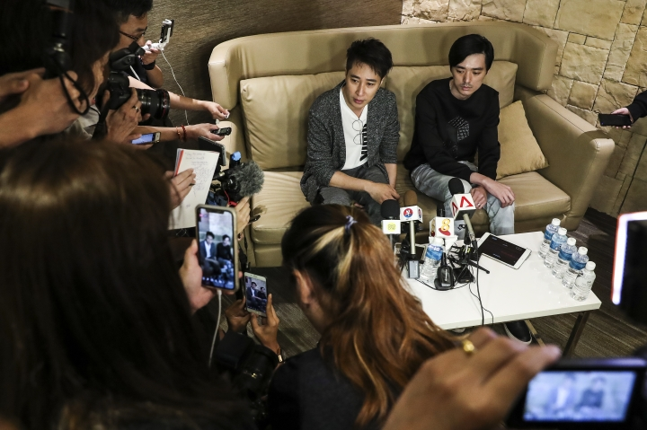 Kenny Pang, Singapore actor Aloysius Pang's elder brother, right, and Dasmond Koh, Pang's agent, speak during a press conference after arriving at Changi Airport in Singapore, Thursday, Jan. 24, 2019. The actor died Wednesday from injuries sustained during a military training exercise in New Zealand. (AP Photo/Yong Teck Lim)