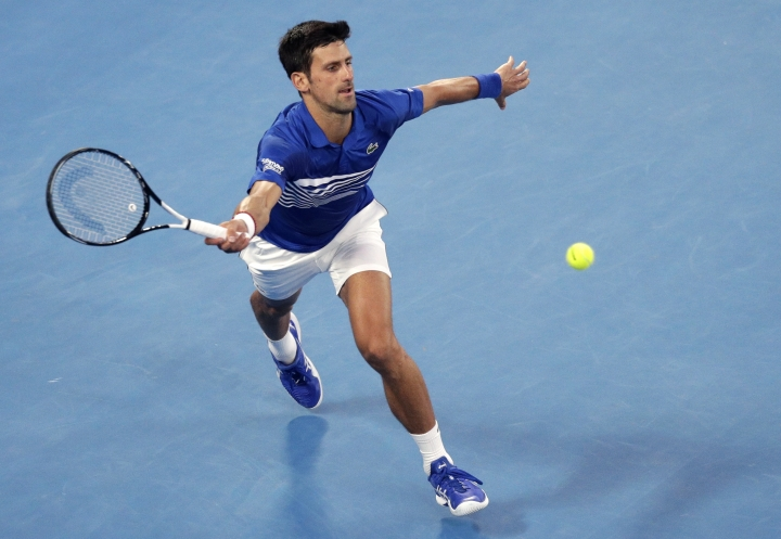 Serbia's Novak Djokovic makes a forehand return to France's Lucas Pouille during their semifinal at the Australian Open tennis championships in Melbourne, Australia, Friday, Jan. 25, 2019. (AP Photo/Kin Cheung)