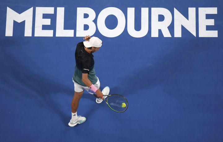 France's Lucas Pouille prepares to serve to Serbia's Novak Djokovic during their semifinal at the Australian Open tennis championships in Melbourne, Australia, Friday, Jan. 25, 2019. (AP Photo/Andy Brownbill)