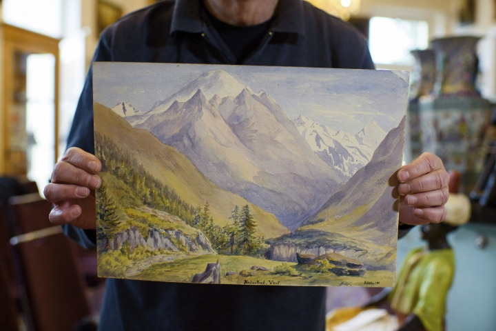 In this Thursday, Jan. 24, 2019 picture an employee of an action house holds a watercolor landscape in Berlin, Germany. Berlin police say three watercolor landscapes allegedly painted by a young Adolf Hitler are being examined by experts to determine if they are fakes. The paintings were seized from a city auction house before they could be sold after they had received a complaint questioning their authenticity. (Gregor Fischer/dpa via AP)