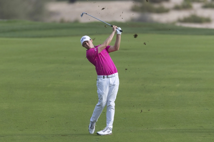 Matthew Fitzpatrick of England hits his second shot on the 14th hole during round two of the Dubai Desert Classic golf tournament in Dubai, United Arab Emirates, Friday, Jan. 25, 2019. (AP Photo/Neville Hopwood)