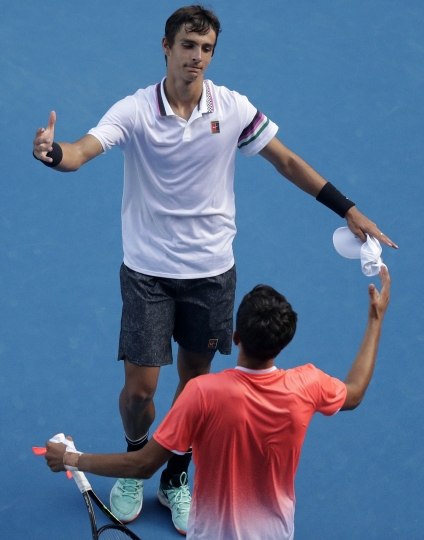 Italy's Lorenzo Musetti, top, is congratulated by United States' Emilio Nava after winning the boy's singles final at the Australian Open tennis championships in Melbourne, Australia, Saturday, Jan. 26, 2019.(AP Photo/Kin Cheung)