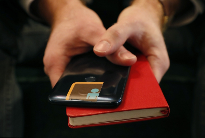 John Scott-Railton, a senior researcher at the Citizen Lab, an internet watchdog group, holds his cell phone which has its camera blocked by an adhesive sticker, as he poses for a photograph, Thursday, Jan. 17, 2019, in New York. The Citizen Lab, an interdisciplinary laboratory based at the Munk School of Global Affairs at the University of Toronto, does research and development at the intersection of digital media, global security, and human rights. Its researchers have recently been targeted by a mysterious group of undercover operatives. (AP Photo/Kathy Willens)