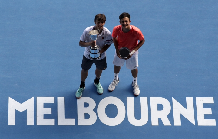 Italy's Lorenzo Musetti, left, holds his trophy after defeating United States' Emilio Nava, right, in the boy's singles final at the Australian Open tennis championships in Melbourne, Australia, Saturday, Jan. 26, 2019. (AP Photo/Kin Cheung)
