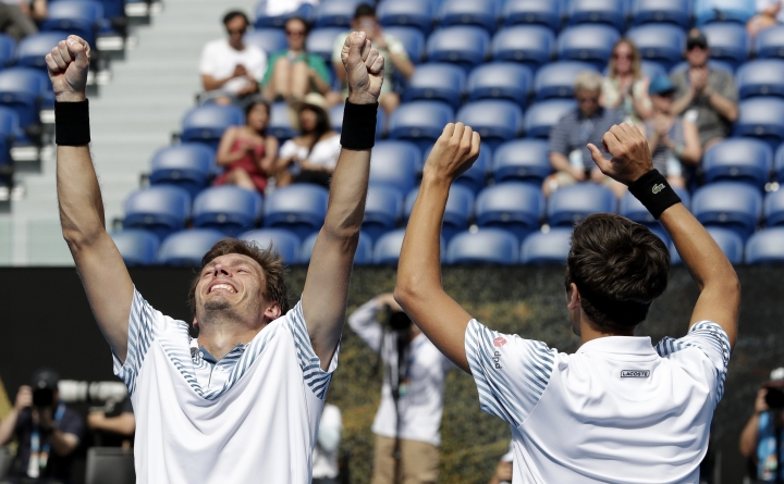 France's Nicolas Mahut, right, and compatriot Pierre-Hugues Herbet celebrate after defeating Finland's Henri Kontinen and Australia's John Peers in the men's doubles final at the Australian Open tennis championships in Melbourne, Australia, Sunday, Jan. 27, 2019.(AP Photo/Aaron Favila)