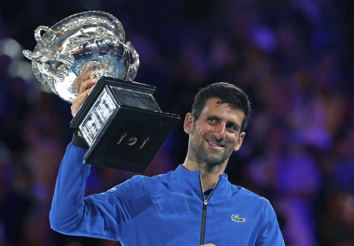 Serbia's Novak Djokovic holds his trophy aloft after defeating Spain's Rafael Nadal in the men's singles final at the Australian Open tennis championships in Melbourne, Australia, Sunday, Jan. 27, 2019. (AP Photo/Kin Cheung)