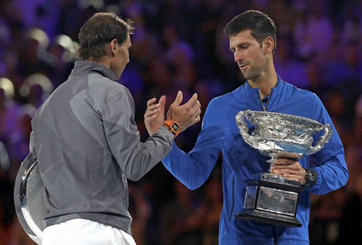 Serbia's Novak Djokovic, right, shakes hands with Spain's Rafael Nadal on the podium after winning the men's singles final at the Australian Open tennis championships in Melbourne, Australia, Sunday, Jan. 27, 2019. (AP Photo/Kin Cheung)
