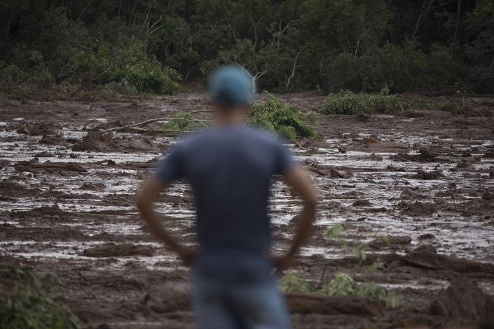 A man looks at the mud after a dam collapse near Brumadinho, Brazil, Saturday, Jan. 26, 2019. Rescuers in helicopters searched for survivors while firefighters dug through mud in a huge area in southeastern Brazil buried by the collapse of a dam holding back mine waste, with at least nine people dead and up to 300 missing. (AP Photo/Leo Correa)
