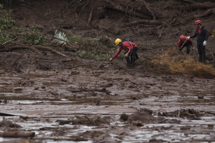 Firefighters search tin he mud, after a dam collapse near Brumadinho, Brazil, Saturday, Jan. 26, 2019. Rescuers in helicopters on Saturday searched for survivors while firefighters dug through mud in a huge area in southeastern Brazil buried by the collapse of a dam holding back mine waste, with at least nine people dead and up to 300 missing. (AP Photo/Leo Correa)