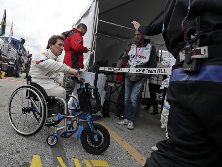 Alex Zanardi heads to his pit stall before taking a turn driving in the IMSA 24 hour auto race at Daytona International Speedway, Saturday, Jan. 26, 2019, in Daytona Beach, Fla. (AP Photo/John Raoux)
