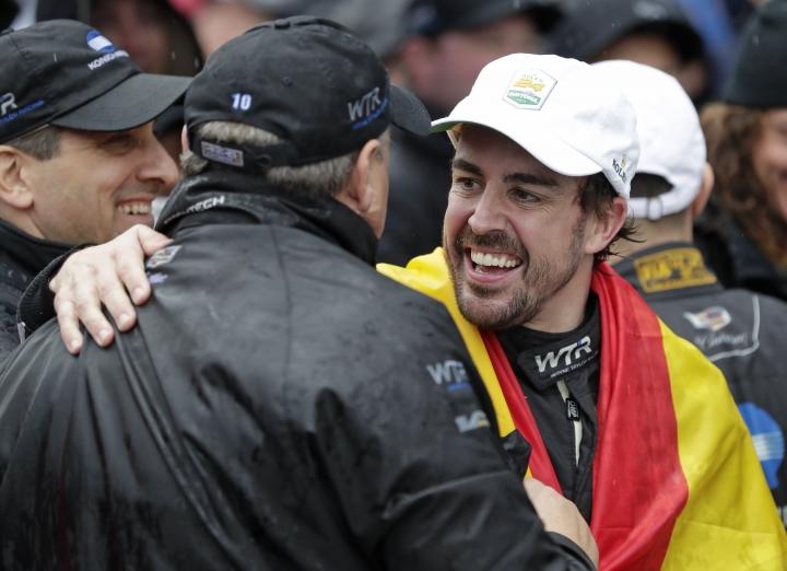 Fernando Alonso,right, of Spain, celebrates with crew members after winning the IMSA 24-hour race at Daytona International Speedway, Sunday, Jan. 27, 2019, in Daytona Beach, Fla. (AP Photo/John Raoux)
