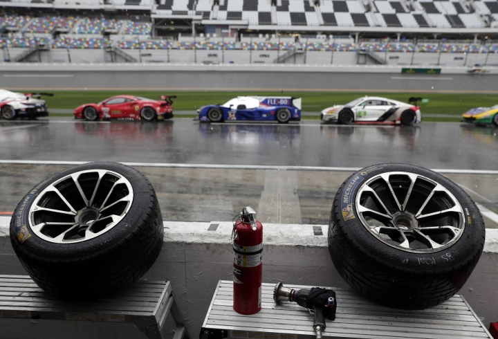 Tires sit idle in a pits stall overlooking pit road where the cars were parked after the IMSA 24-hour race was red-flagged because of rain at Daytona International Speedway, Sunday, Jan. 27, 2019, in Daytona Beach, Fla. (AP Photo/John Raoux)