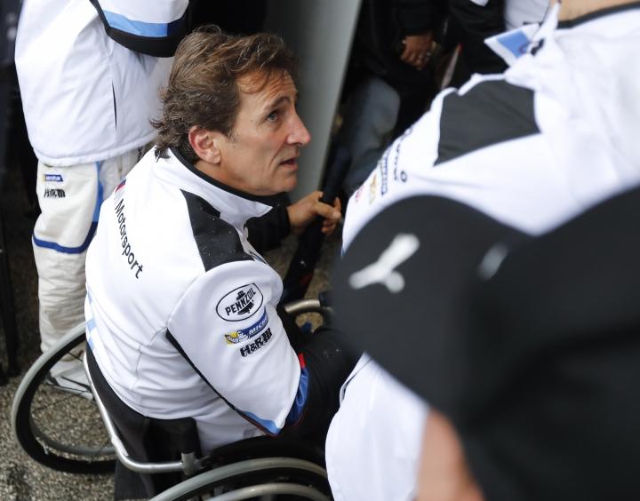 Alex Zanardi talks with crew members in his pit stall during the IMSA 24-hour race at Daytona International Speedway, Sunday, Jan. 27, 2019, in Daytona Beach, Fla. (AP Photo/Terry Renna)