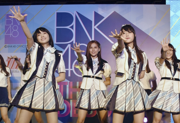 FILE - In this June 2, 2017, file photo, Thai pop band BNK 48 performs for the first time in a large commercial facility in Bangkok, Thailand. The popular Thai music act BNK 48 has set off a scandal after one of its members wore a shirt showing the swastika flag of Nazi Germany during a performance. (The Yomiuri Shimbun via AP Images)