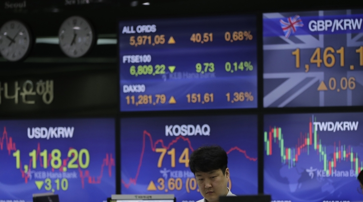 A currency trader stands near the screens showing the foreign exchange rates at the foreign exchange dealing room in Seoul, South Korea, Monday, Jan. 28, 2019. Markets are higher in Asia after President Donald Trump ended the partial U.S. government shutdown. (AP Photo/Lee Jin-man)