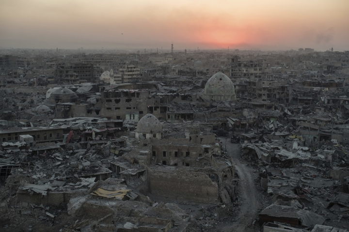 FILE - In this July 11, 2017 file photo, the sun sets behind destroyed buildings in the west side of Mosul, Iraq. For centuries, residents of Mosul have spoken a unique form of Arabic enriched by the Iraqi city's long history as a crossroads of civilization, a singsong dialect that many now fear will die out after years of war and displacement. Much of Mosul's Old City, where speakers of the dialect are concentrated, was completely destroyed in the war against the Islamic State group. (AP Photo/Felipe Dana, File)