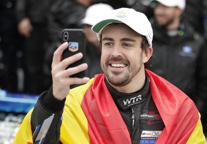 Fernando Alonso, of Spain, takes a selfie photo in Victory Lane after winning the IMSA 24 hour race at Daytona International Speedway, Sunday, Jan. 27, 2019, in Daytona Beach, Fla. (AP Photo/John Raoux)