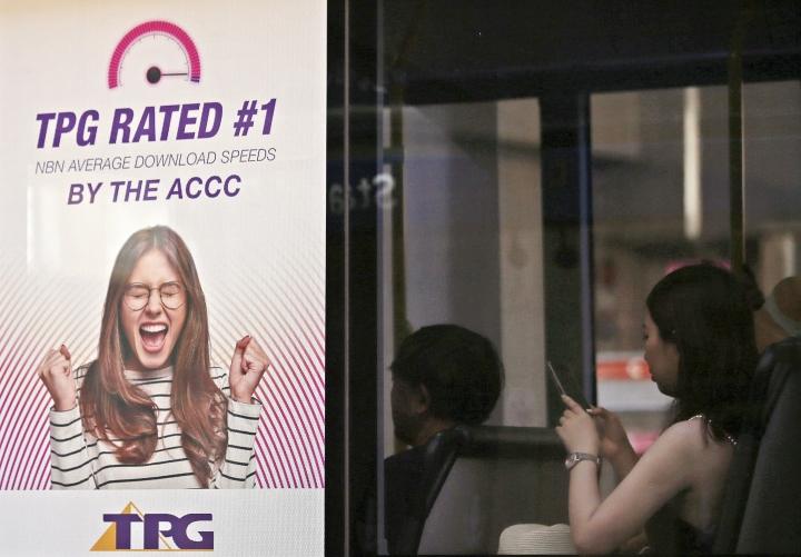 A woman uses a mobile device as she sits on a bus branded with a TPG ad at a bus stop in Sydney, Tuesday, Jan. 29, 2019. TPG Telecom said it had abandoned the rollout of what would have been Australia's fourth mobile network because of the government's ban on Chinese giant Huawei, which would have been the main equipment vendor. (AP Photo/Rick Rycroft)