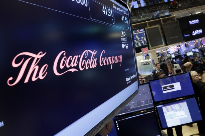 FILE - In this Friday, Dec. 9, 2016 file photo, the Coca-Cola logo appears above the post where it trades on the floor of the New York Stock Exchange. With obesity becoming a more pressing global problem, two January 2109 reports in science journals are calling for policies that limit industry influence and reviving debate about what role food companies should play in public health efforts. (AP Photo/Richard Drew)