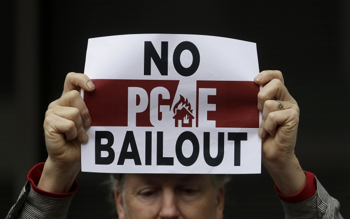 A man holds up a sign at a rally before a California Public Utilities Commission meeting in San Francisco, Monday, Jan. 28, 2019. California regulators have approved a measure allowing Pacific Gas & Electric Corp. to immediately obtain credit and loans while the company is under Chapter 11 bankruptcy protection. (AP Photo/Jeff Chiu)