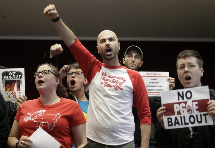 Brandon Harami, center, and others yell during a California Public Utilities Commission meeting in San Francisco, Monday, Jan. 28, 2019. California regulators have approved a measure allowing Pacific Gas & Electric Corp. to immediately obtain credit and loans while the company is under Chapter 11 bankruptcy protection. (AP Photo/Jeff Chiu)